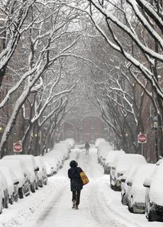 Pedestrians made their way up a freshly snow-covered Garden Street on Beacon Hill on Wednesday.